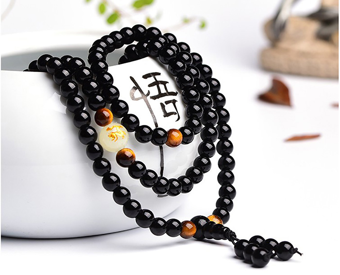 Buddhist mala bracelet leaning on a bowl