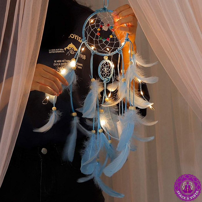 man holding blue color dream catcher with LED lamps