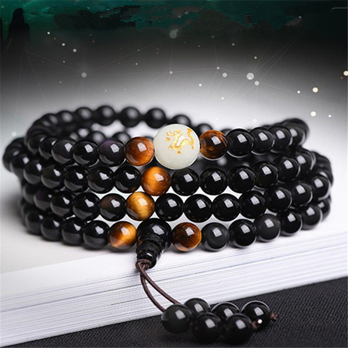 natural Obsidian Buddhist mala bracelet on a book