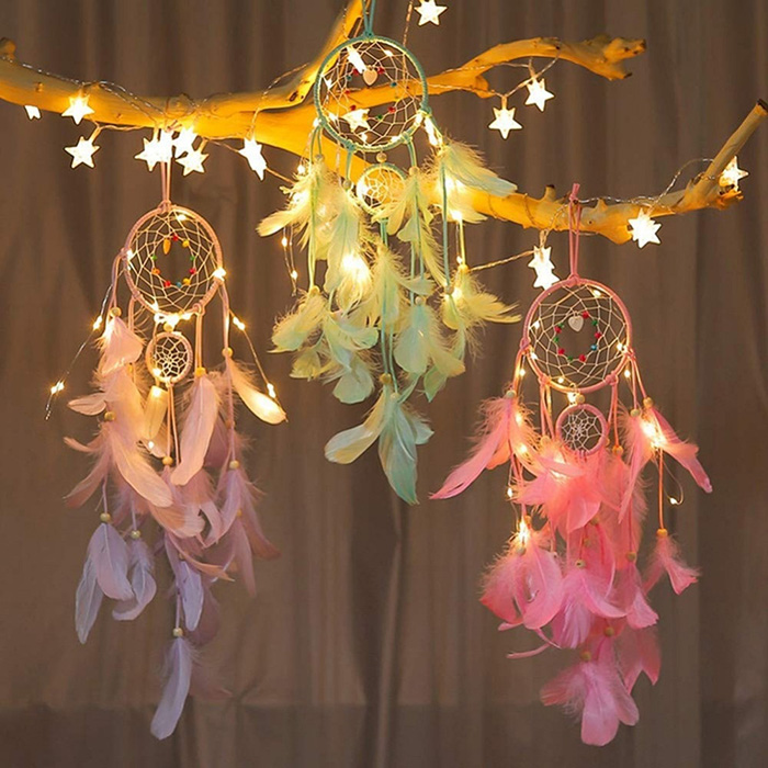 three dream catchers hanging on a branch