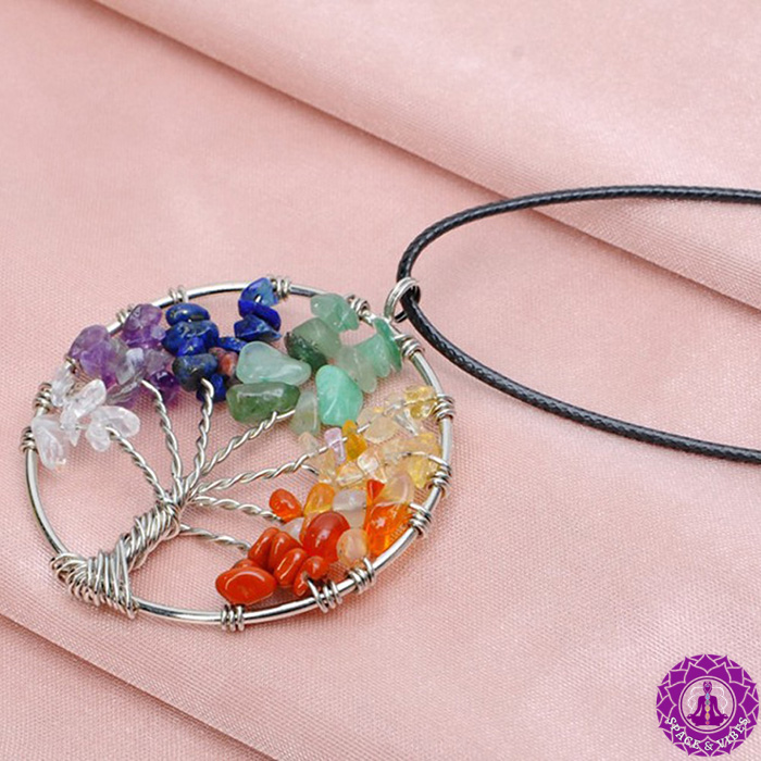 tree of life necklace pendant with chakra color stones laid on a fabric
