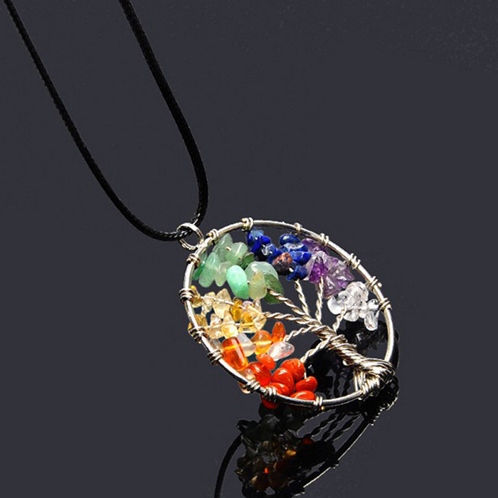 tree of life necklace pendant with stones in seven chakra colors on a black background