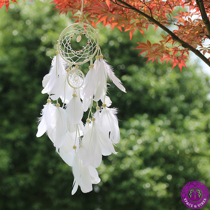 white dream catcher hanging on the branch
