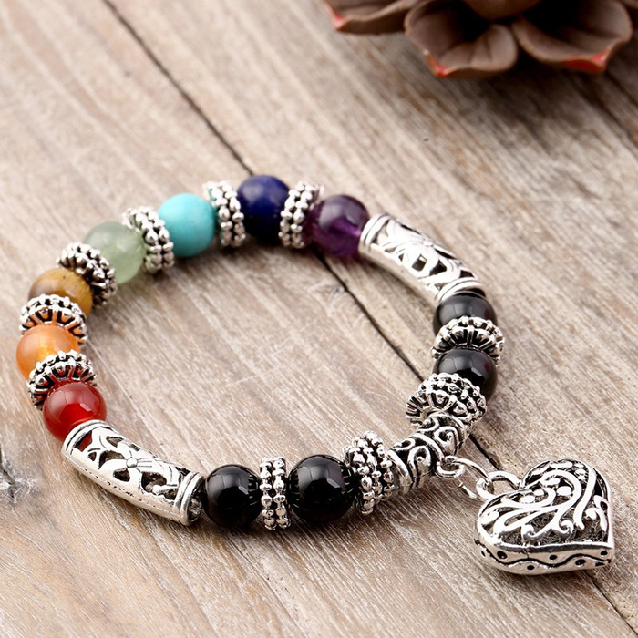 woman bracelet with natural stones in seven chakras colors and heart pendant laid on a desk