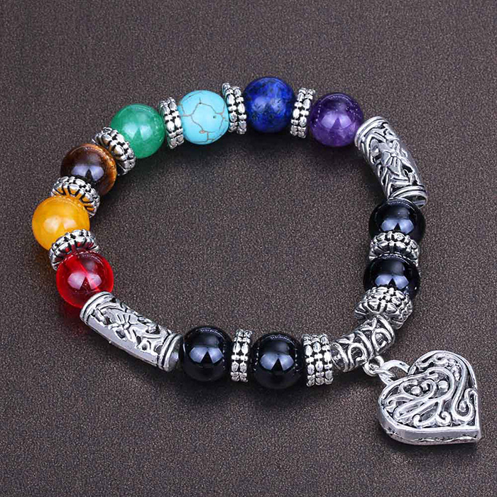 woman bracelet with natural stones in seven chakras colors and heart pendant on a black background