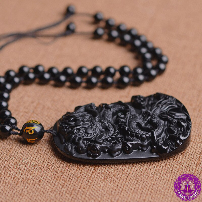 Anicent black obsidian dragon necklace laid on a desk
