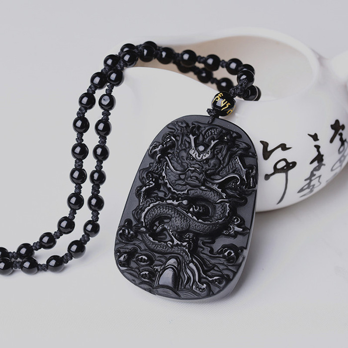 Anicent black obsidian dragon necklace leaning on a bowl
