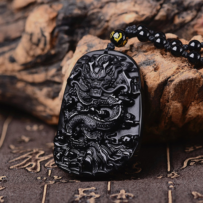 Anicent black obsidian dragon necklace leaning on a rock