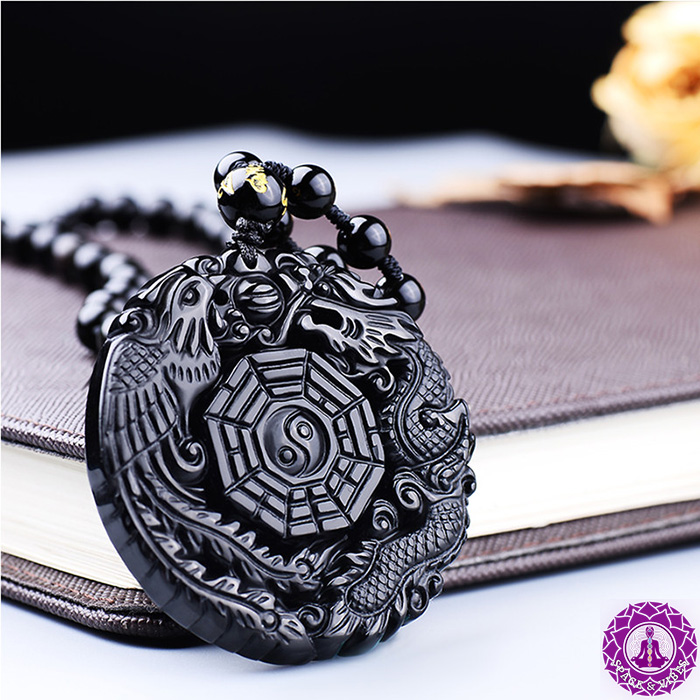 Black Obsidian dragon and phoenix lucky necklace leaning on notebook