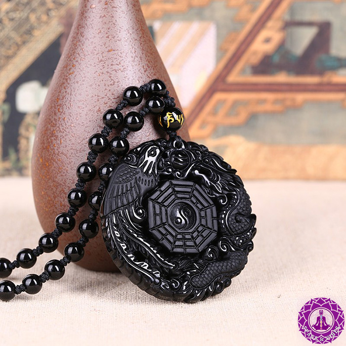 Black Obsidian dragon and phoenix lucky necklace leaning on room freshener