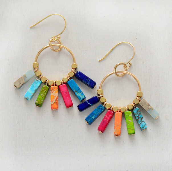 earring with stones in seven chakras colors on a gray background