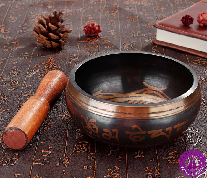 side view to Tibetan singing bowl and its stick