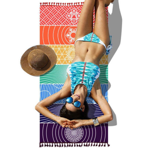 woman in bikini lying on a tapestry in seven chakras colors