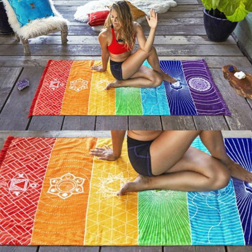 woman sitting on a tapestry in seven chakras colors