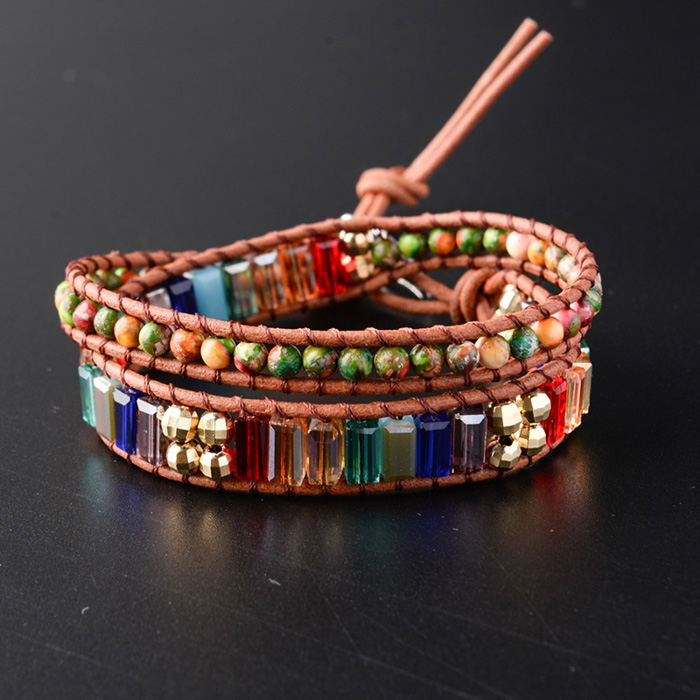 woman wrap bracelet made of healing crystals in seven chakras colors
