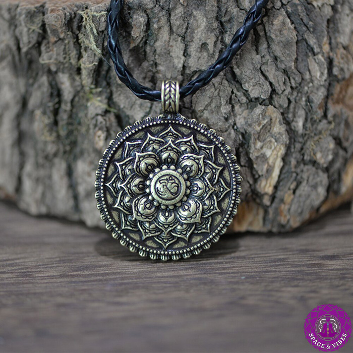 Om and Lotus Antique pendant leaning on the wood