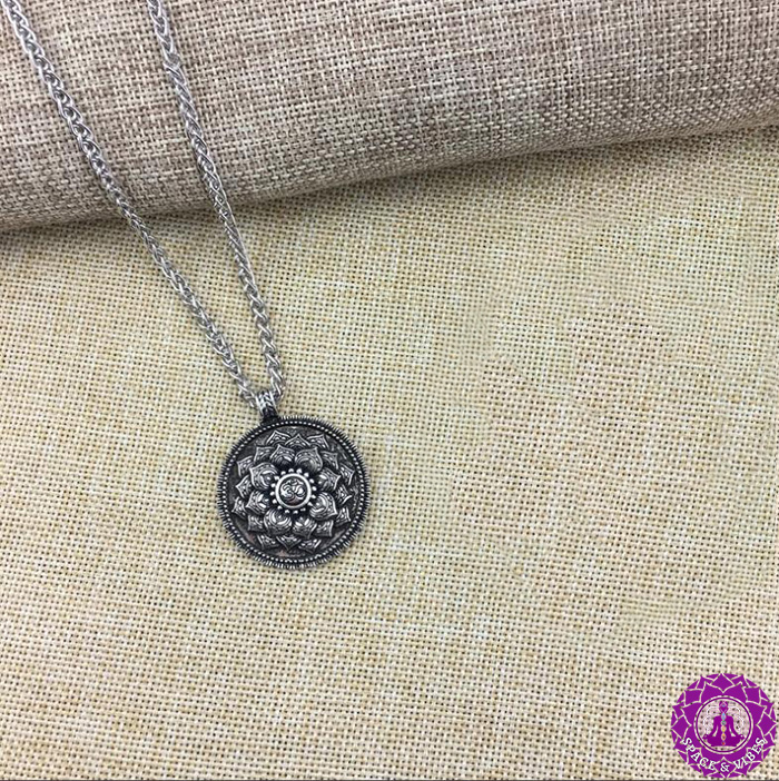 Om and Lotus Antique pendant with metal chain on a textile