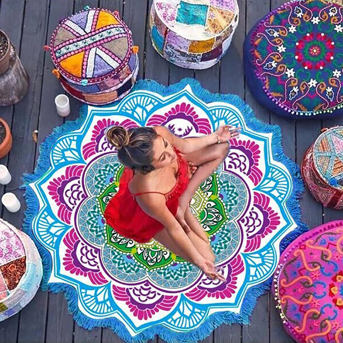a woman in meditation pose sitting on colorful Mandala mat