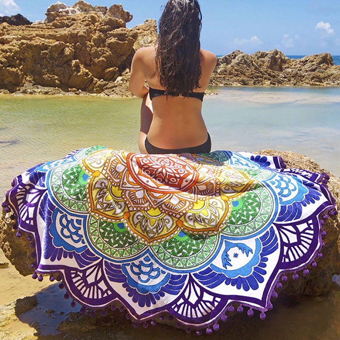 a woman sitting on colorful Mandala towel next to the sea
