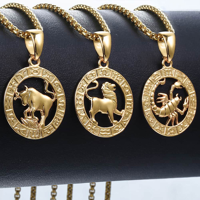 taurus and lion and scorpio horoscope sign necklaces hanging on a jewelry stand