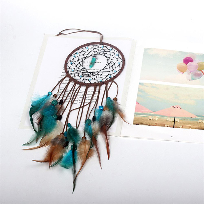 dream catcher with the crystal in the middle of its net laid on a magazine