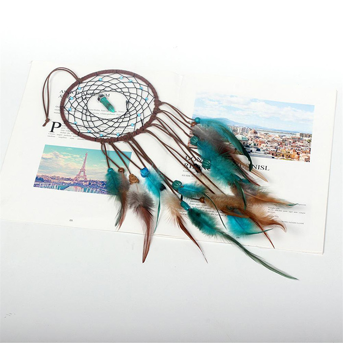 side view of dream catcher with the crystal in the middle of its net laid on a magazine