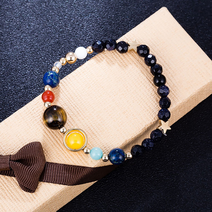 solar system bracelet laid on its package