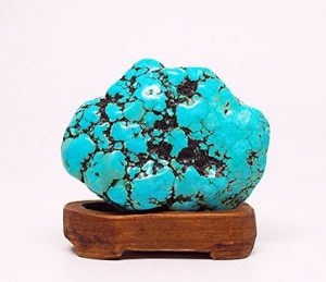 Turquoise semi precious healing stone on a wooden stand