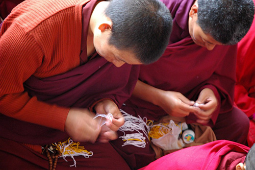 Buddhist monks while knitting lucky bracelets and recite mantras