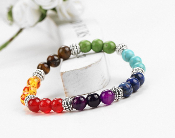 bracelet with stone beads in seven chakra colors leaning on a wooden stick