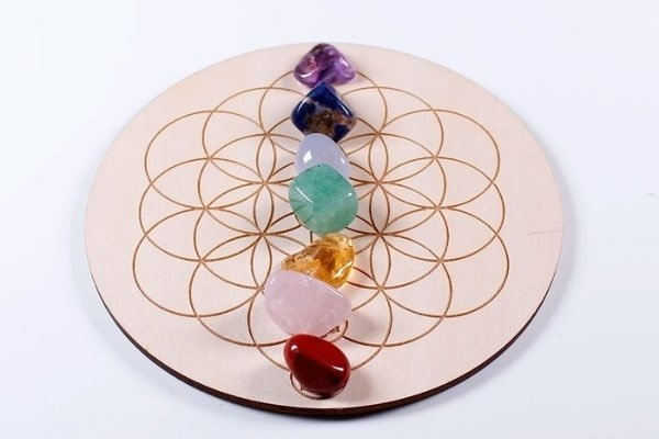 7 chakra stones on wooden plate